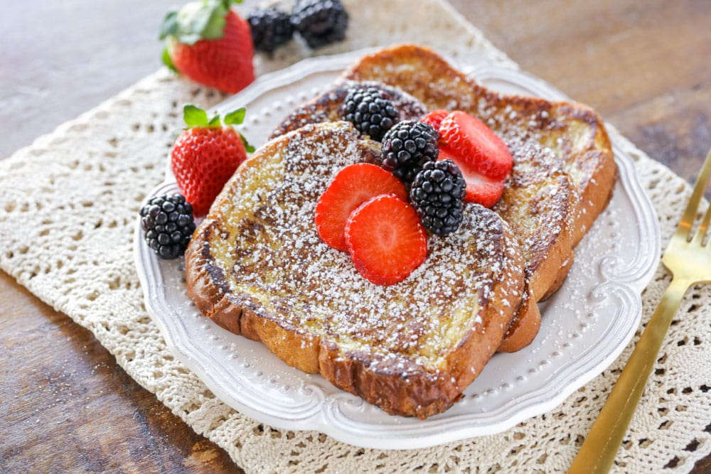 Brioche french toast topped with powdered sugar and berries
