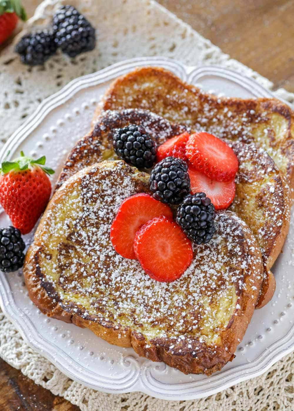 Close up of brioche french toast recipe with berries and powdered sugar