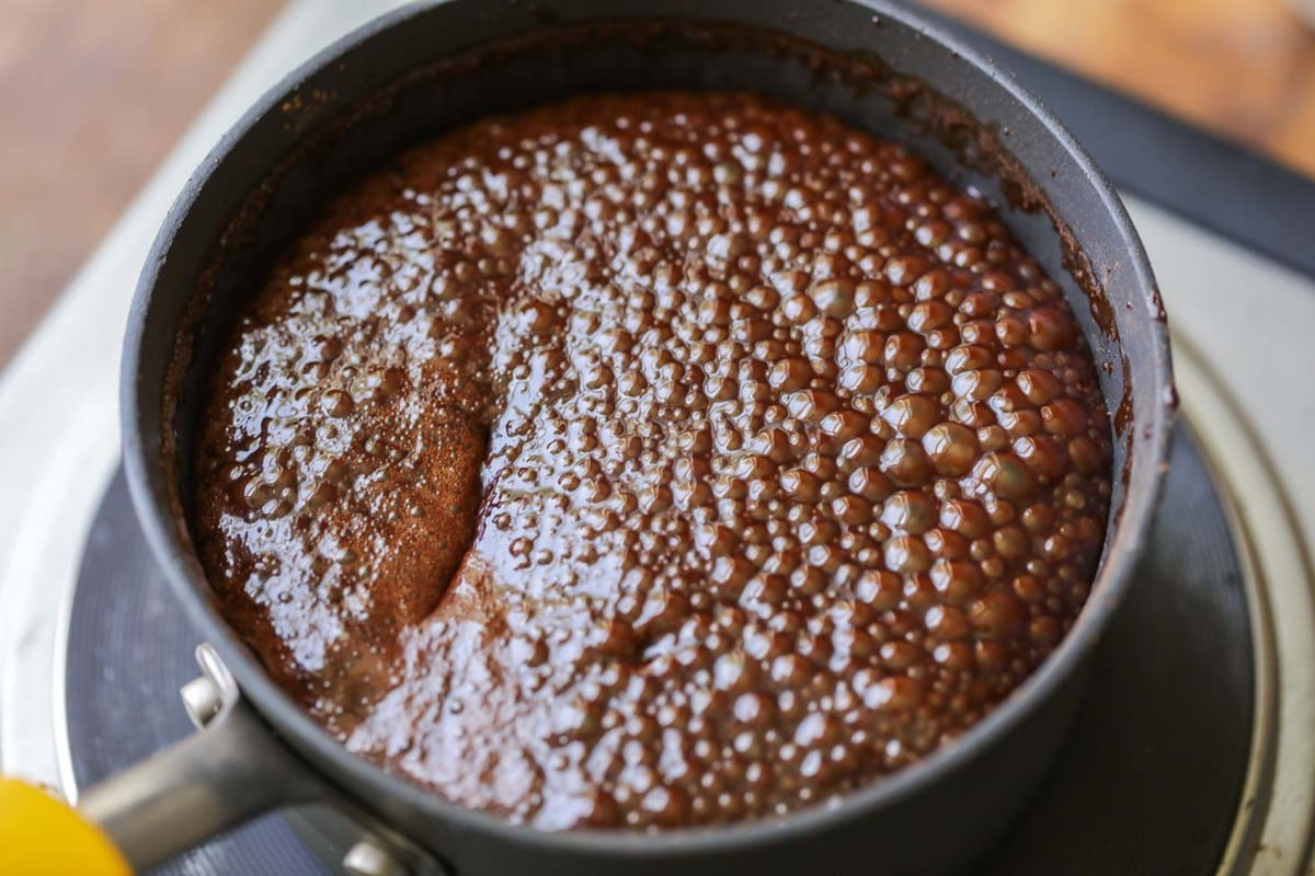 Homemade chocolate syrup boiling in a saucepan