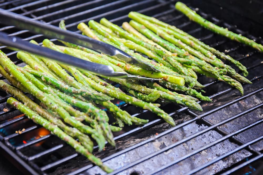 Grilling asparagus on the grill with tongs