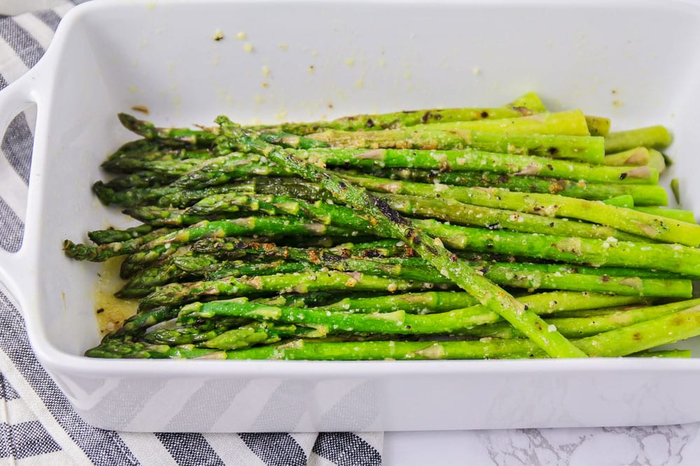 Grilled asparagus in a white serving dish