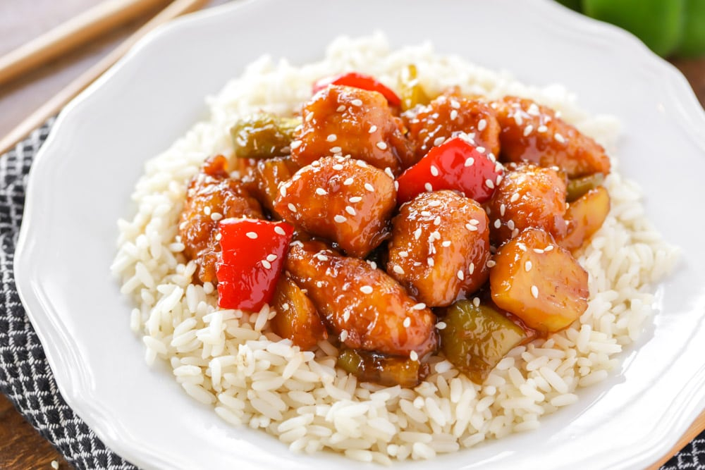 Sweet and sour chicken over white rice on a plate