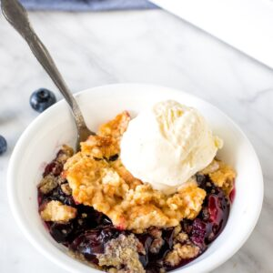 Bowl of blueberry dump cake with a scoop of vanilla ice cream.