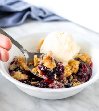 Close up of a spoonfull of blueberry dump cake.
