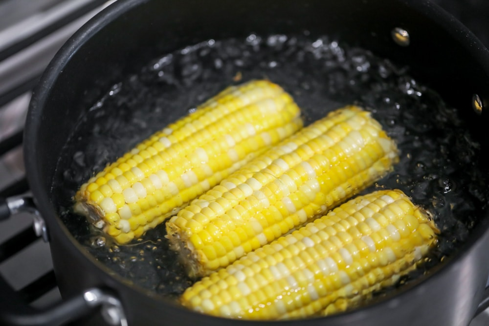 Boiling corn on the cob in a pot on the stove