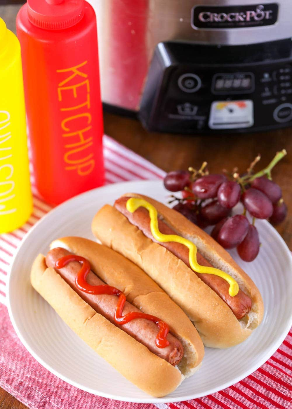 Crock pot hot dogs on a plate topped with ketchup and mustard