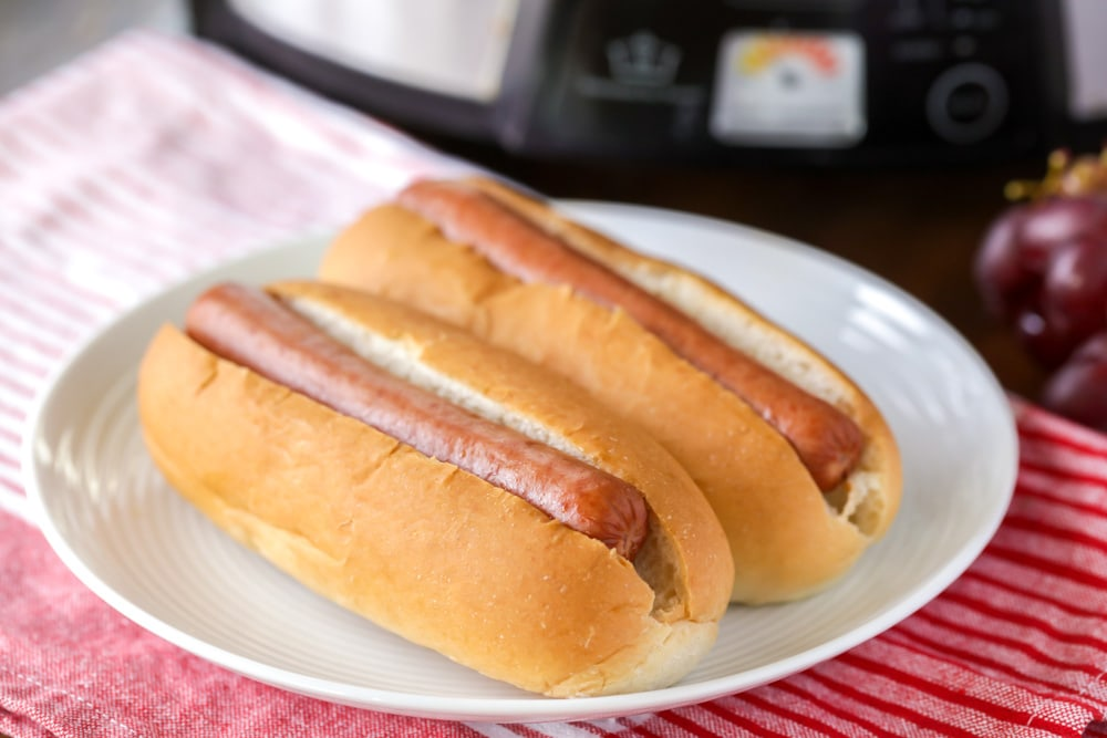 Slow cooker hot dogs inside buns on a plate