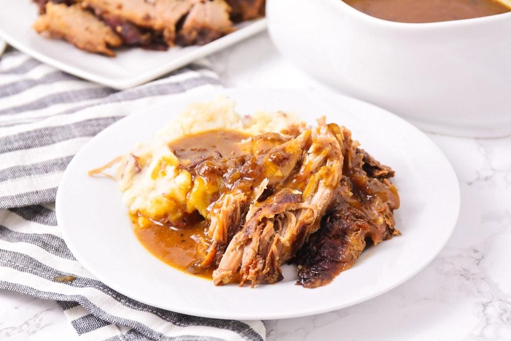 Crock pot pork roast on a white plate with a side of potatoes