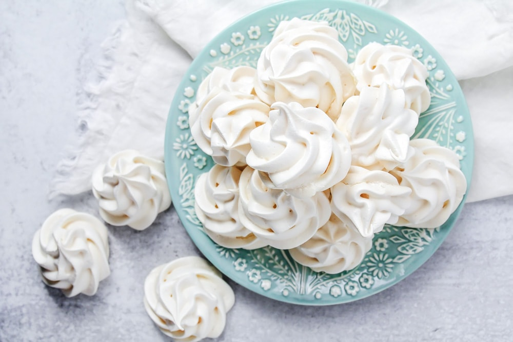 Meringue cookies stacked on a blue plate