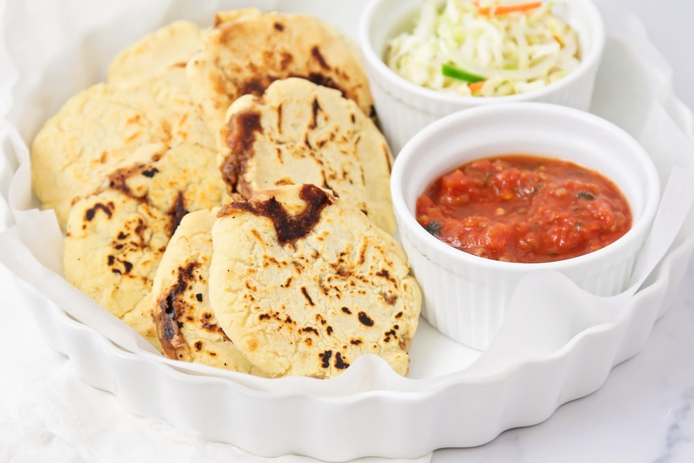 Pupusas on a platter with a side of coleslaw and salsa
