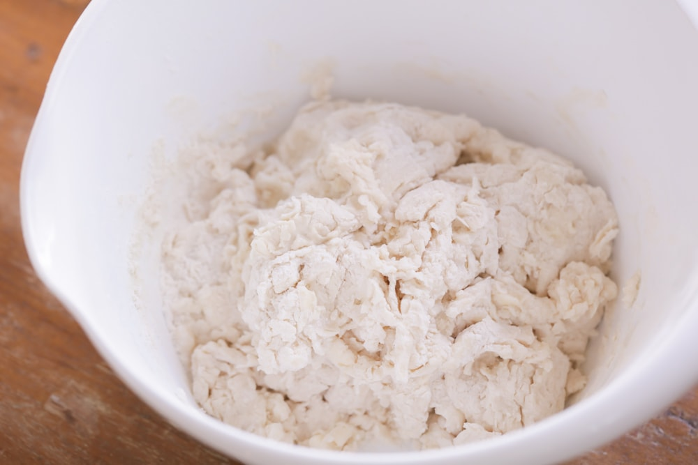 Buttermilk biscuit dough in a white mixing bowl