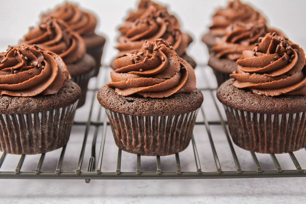 Chocolate buttercream frosting on top of chocolate cupcakes