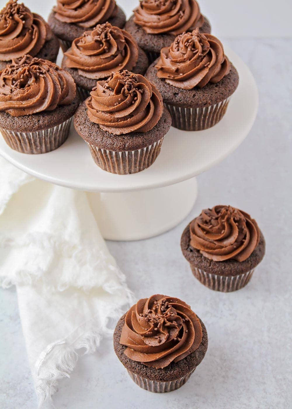 Best chocolate cupcakes on a white cake stand