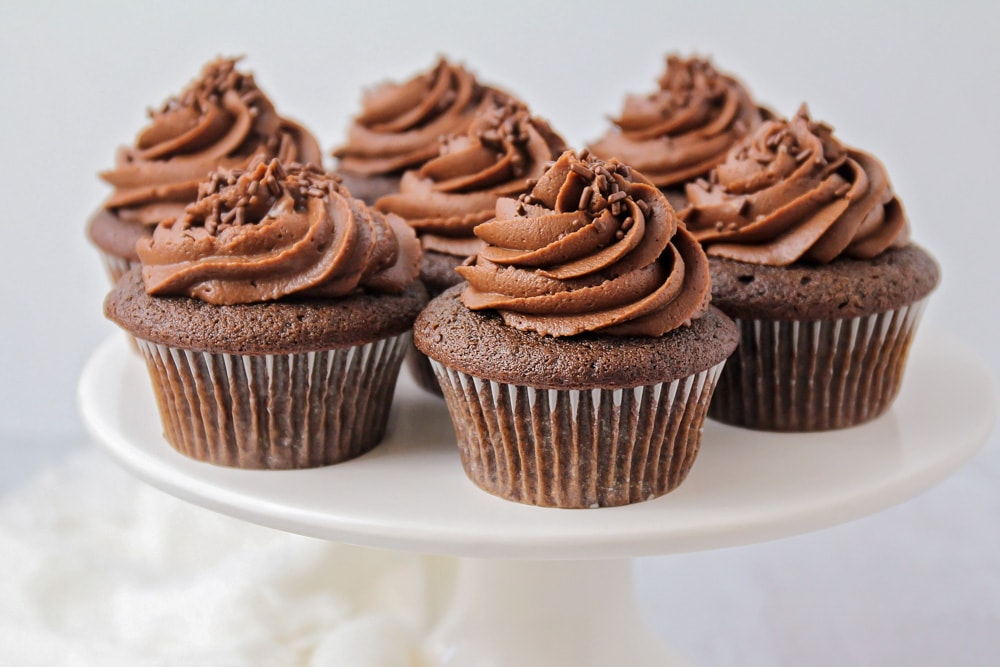 Chocolate cupcakes on a white cake stand