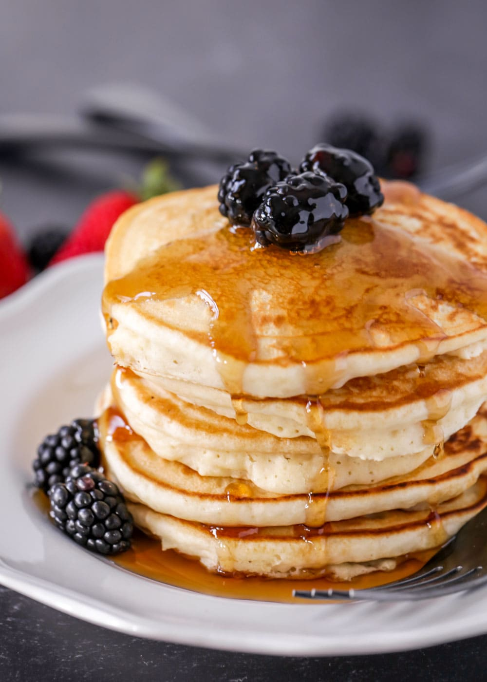 Easy pancake recipe stacked on plate with syrup