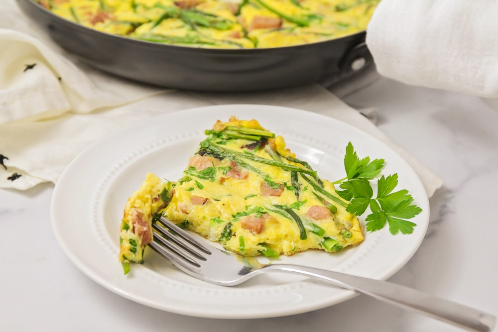 Egg frittata with asparagus and ham on a white plate