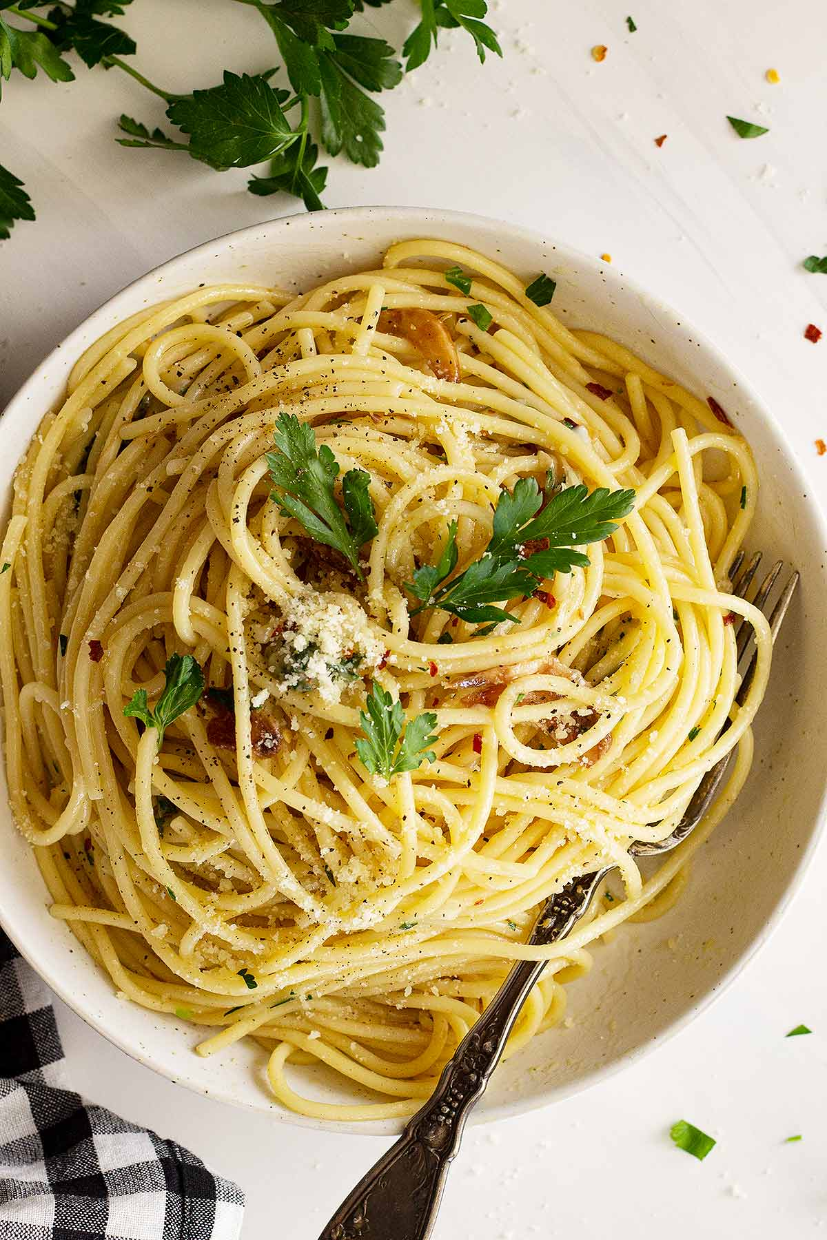 Spaghetti Aglio e Olio topped with parmesan and herbs in a white bowl