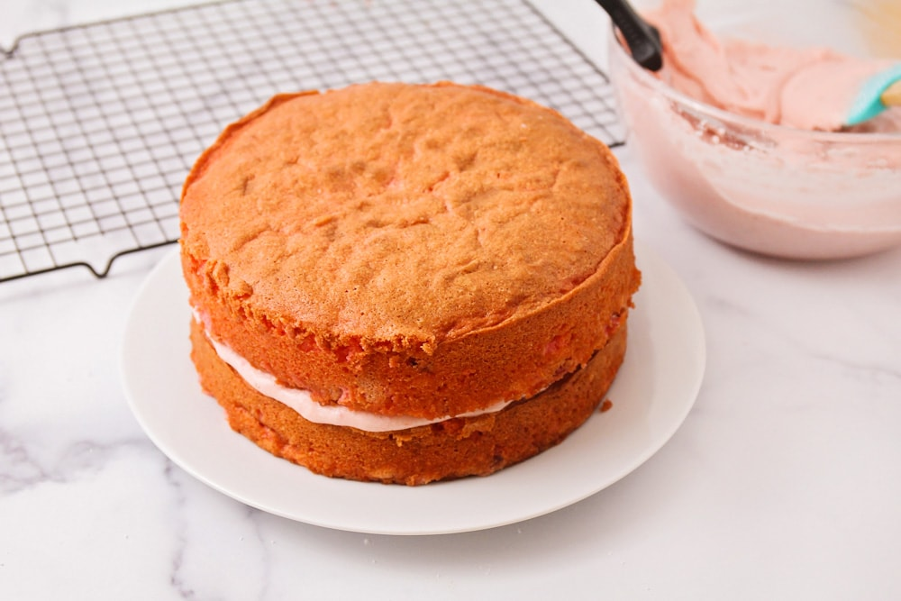 Layering fresh strawberry cake with frosting in between