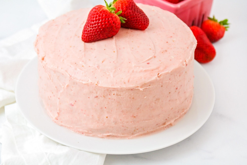 Strawberry cake from scratch with frosting and fresh strawberries on top