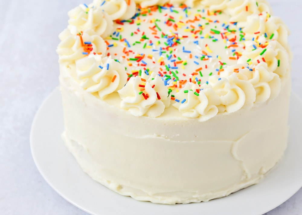 Vanilla cake with vanilla frosting and rainbow sprinkles