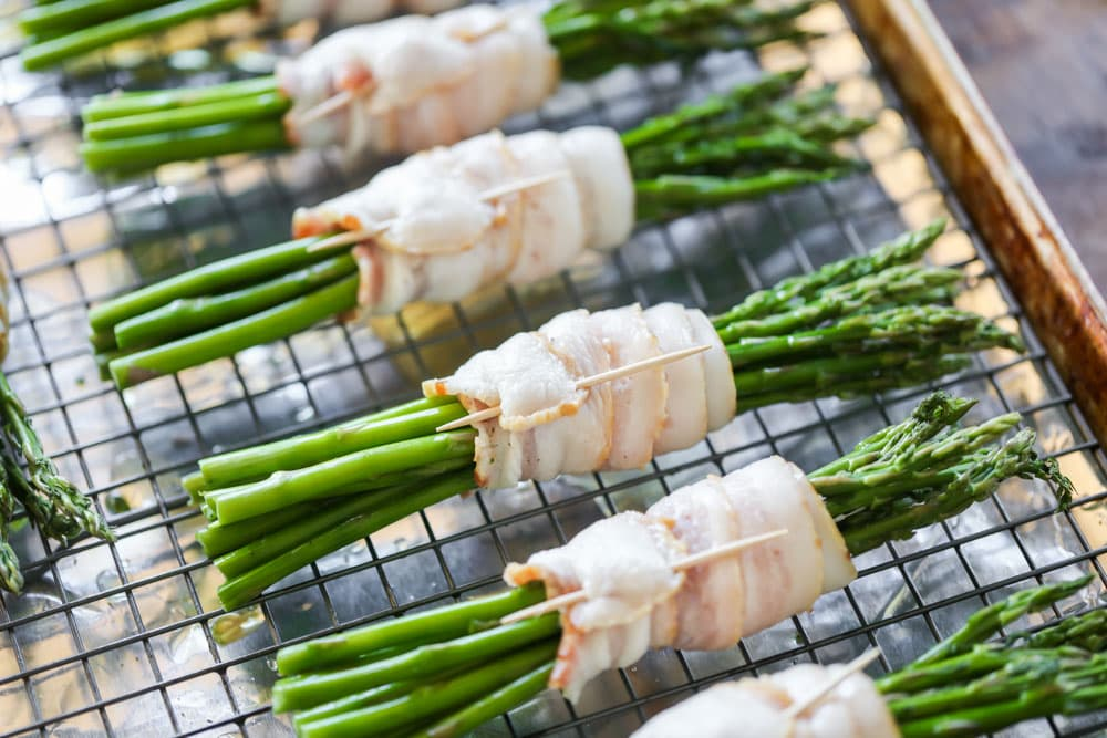 Skewered bacon wrapped asparagus bundles on a sheet pan.