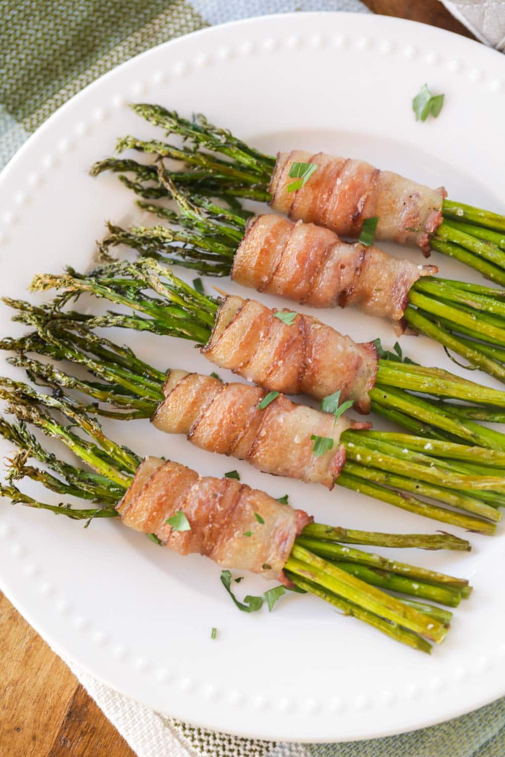 Baked bacon wrapped asparagus bundles on a white plate