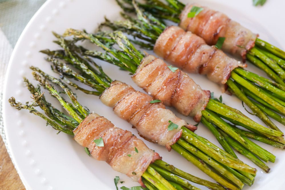 Bacon wrapped asparagus bundles on a white plate.