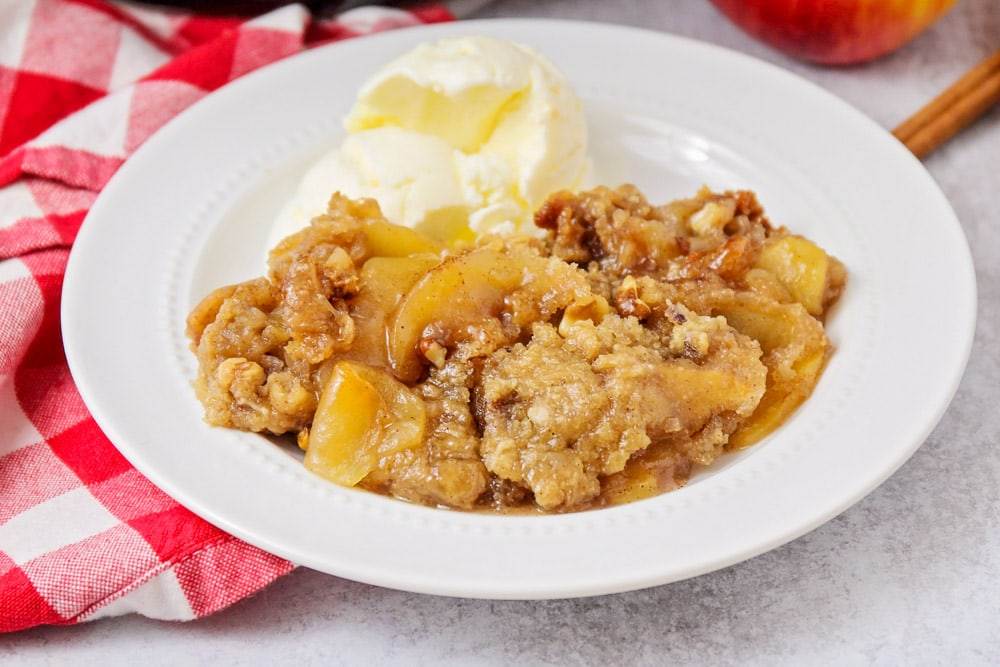 Crock pot apple crisp in bowl with ice cream