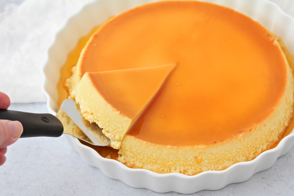 A slice of flan being cut with a serving utensil