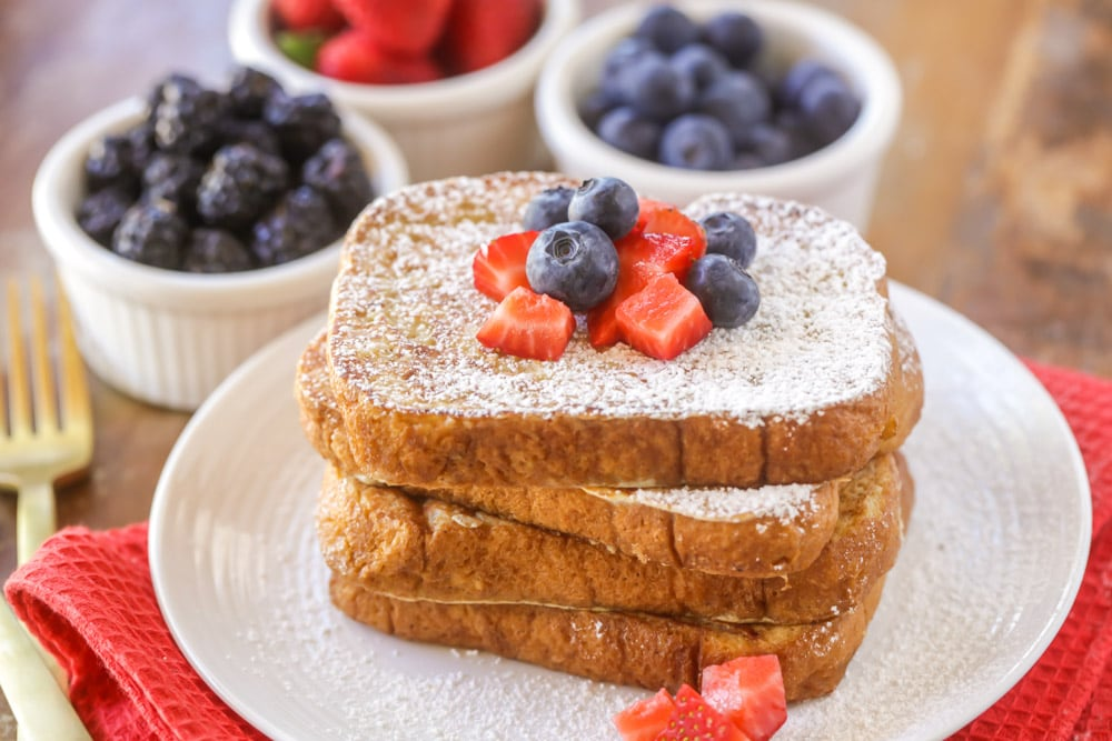 A stack of fluffy french toast on a white plate