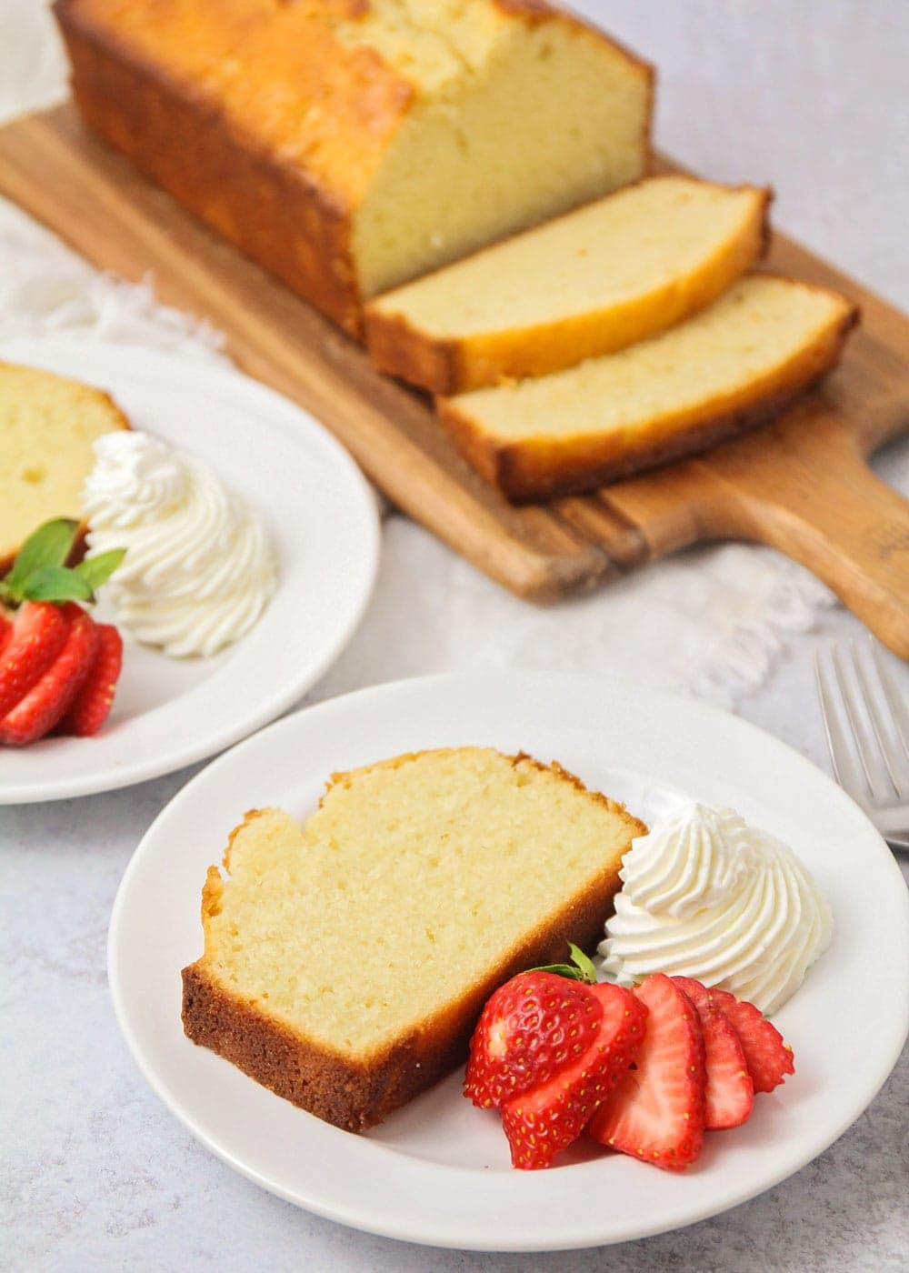 A slice of pound cake on a white plate