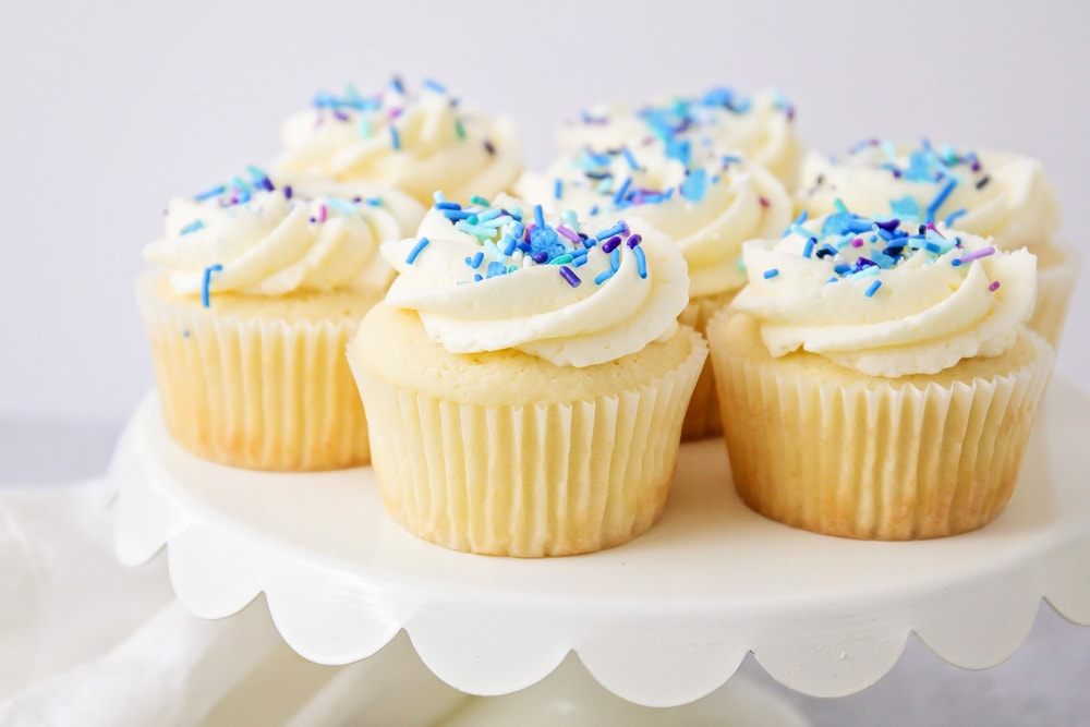 Vanilla cupcakes topped with frosting and sprinkles