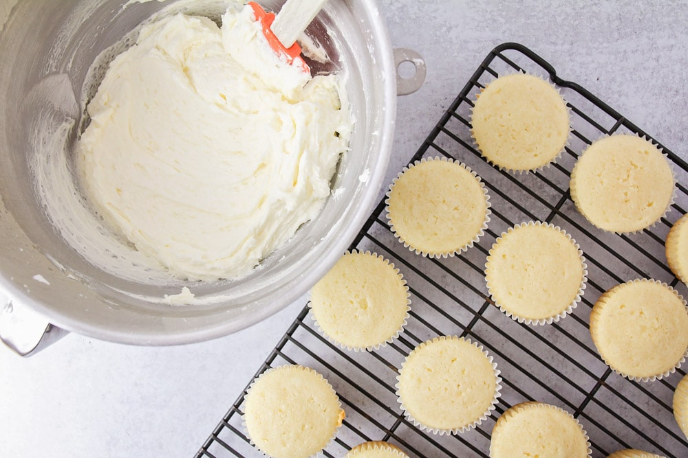 Homemade vanilla cupcakes on a cooling rack next to cupcake frosting