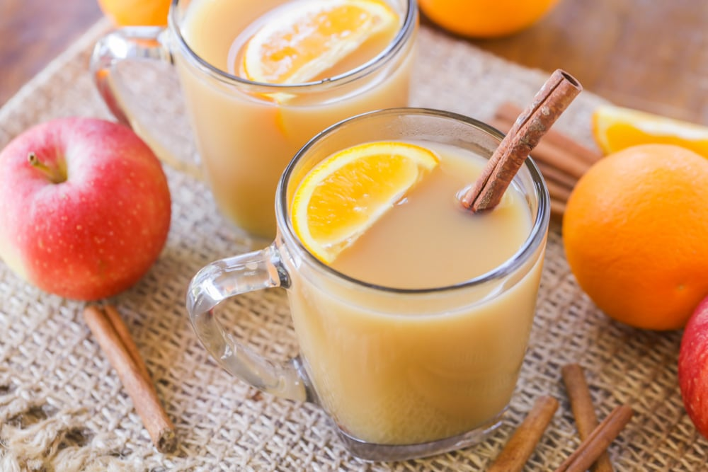 Wassail in a glass mug with an orange slice and cinnamon stick