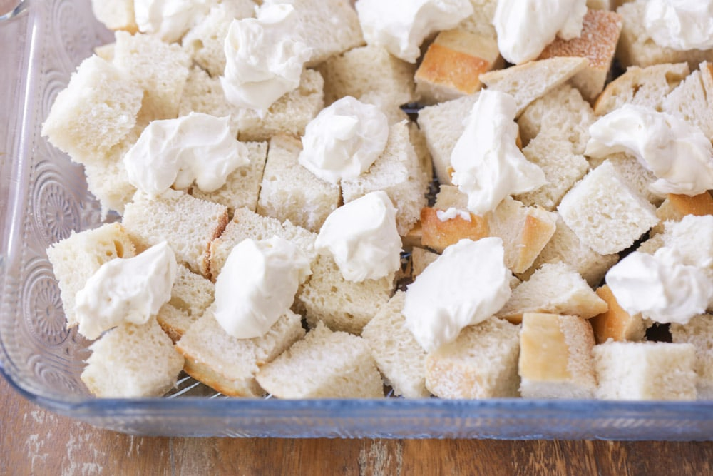 Bread cubes and dollops of cream cheese in a glass casserole dish