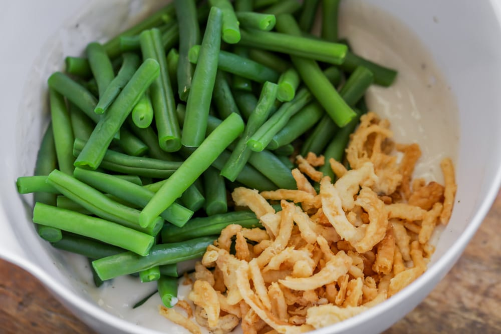 Ingredients for fresh green bean casserole in a mixing bowl