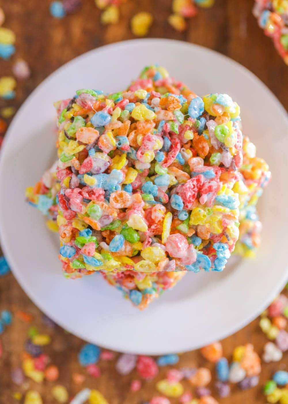 Fruity pebble rice krispie treats stacked on a white plate