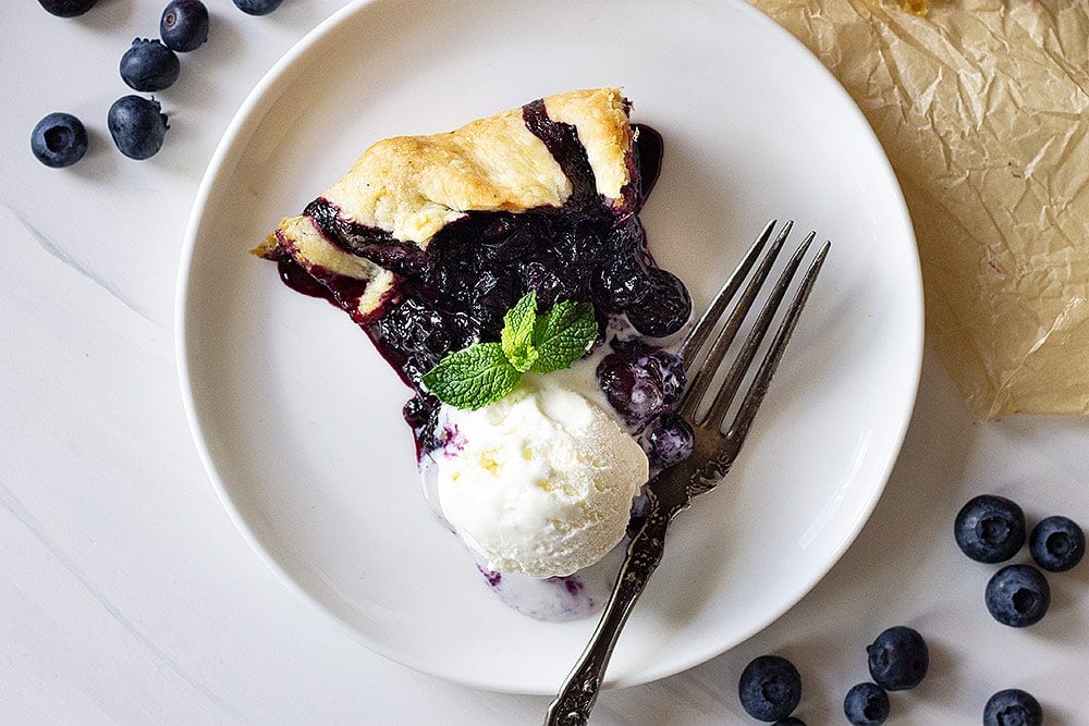 A slice of blueberry galette on a plate with a scoop of vanilla ice cream