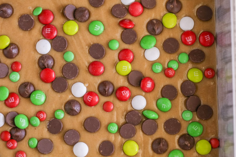 Christmas M&M's and chocolate chips sprinkled on cookie bar dough