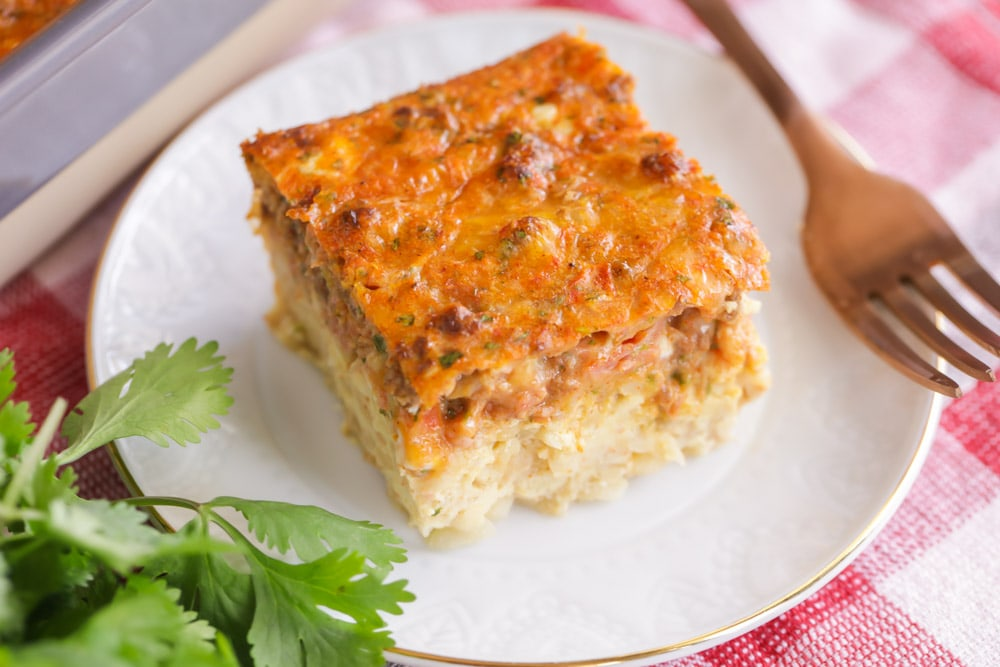 A slice of Mexican breakfast casserole on a white plate