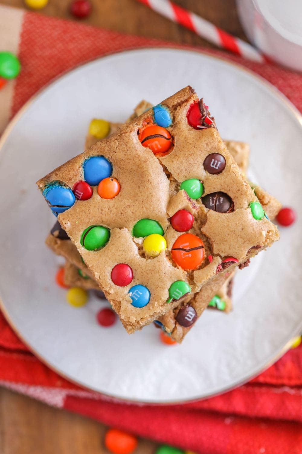 A stack of M&M Cookie Bars on a white plate