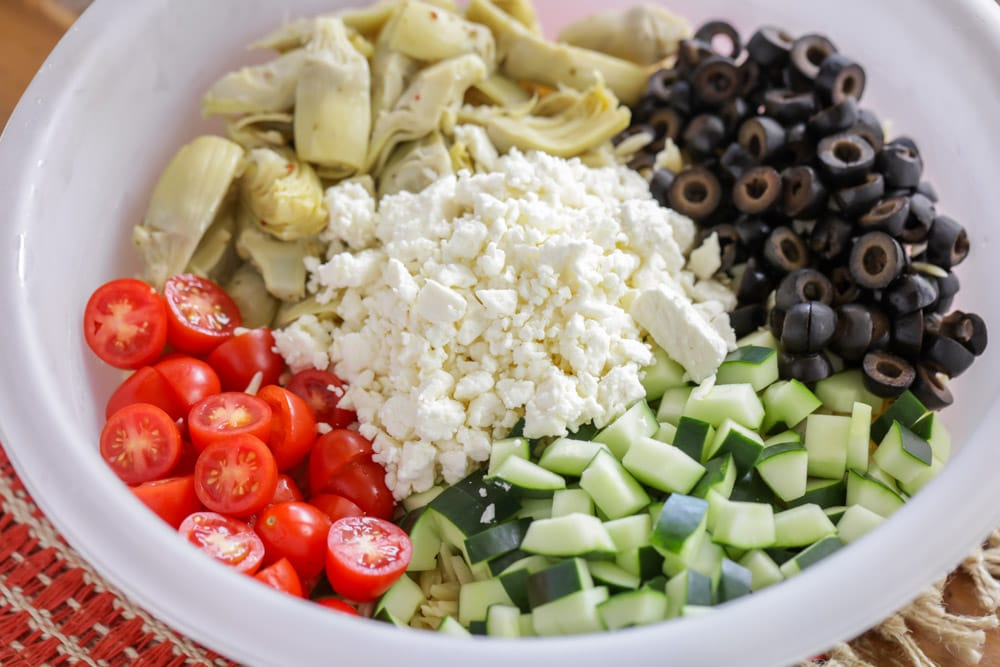 Ingredients for orzo pasta salad recipe in a mixing bowl