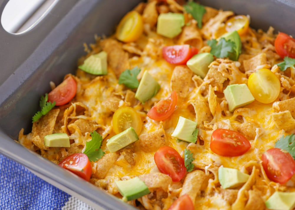 Frito pie topped with avocados and tomatoes