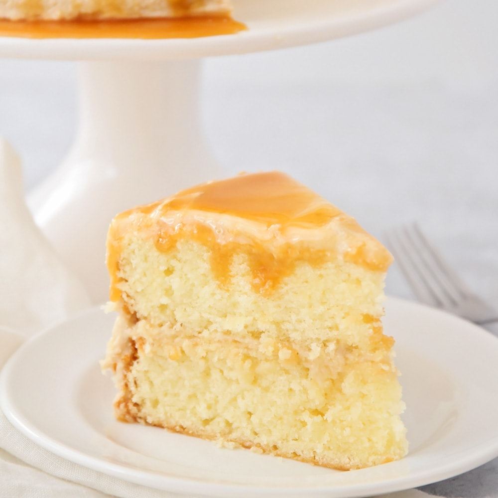 A slice of caramel cake on a white plate