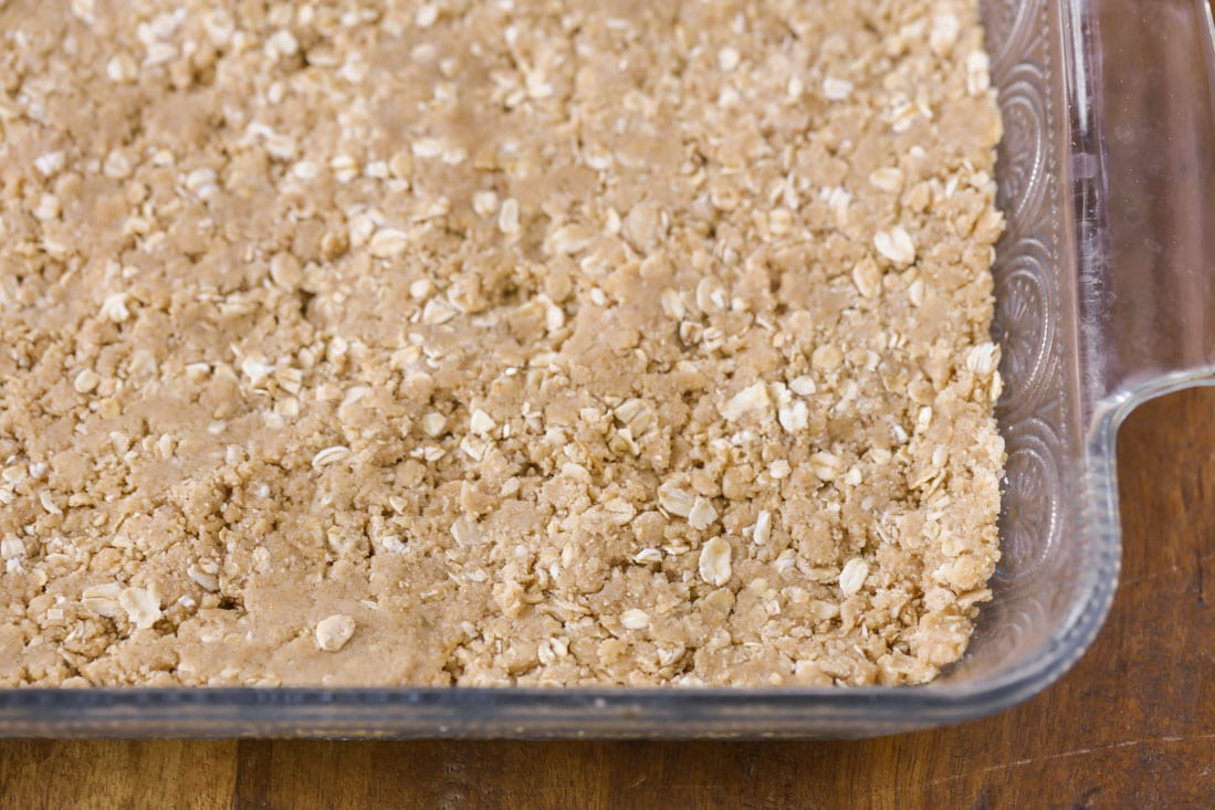 The oat layer of monster cookie bars in a glass baking dish