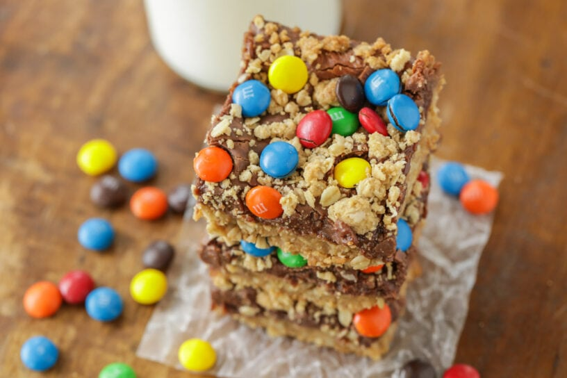 Monster cookie bars stacked on a piece of parchment paper