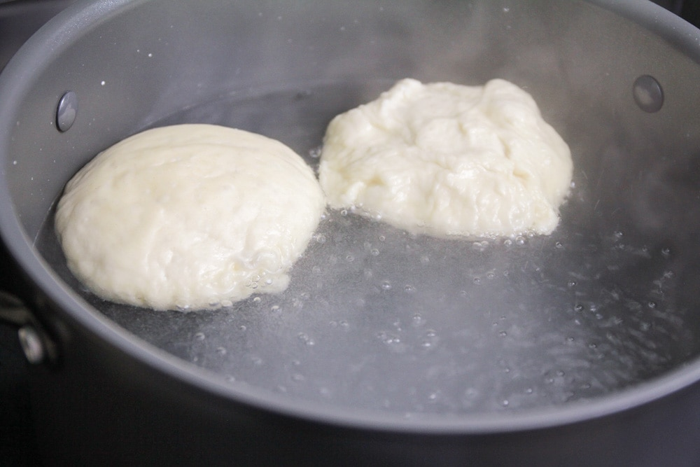 Boiling the pretzel roll dough in a pot