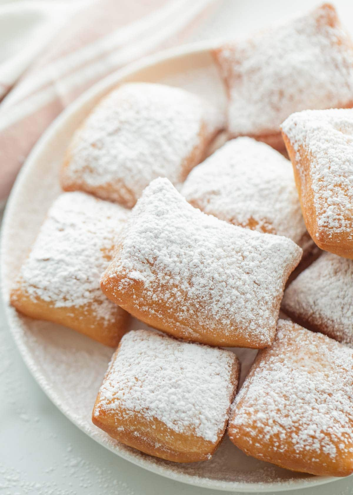 powder sugar coated beignets on a white plate