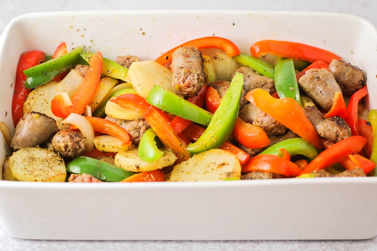 Sausage and potatoes in a white casserole dish.