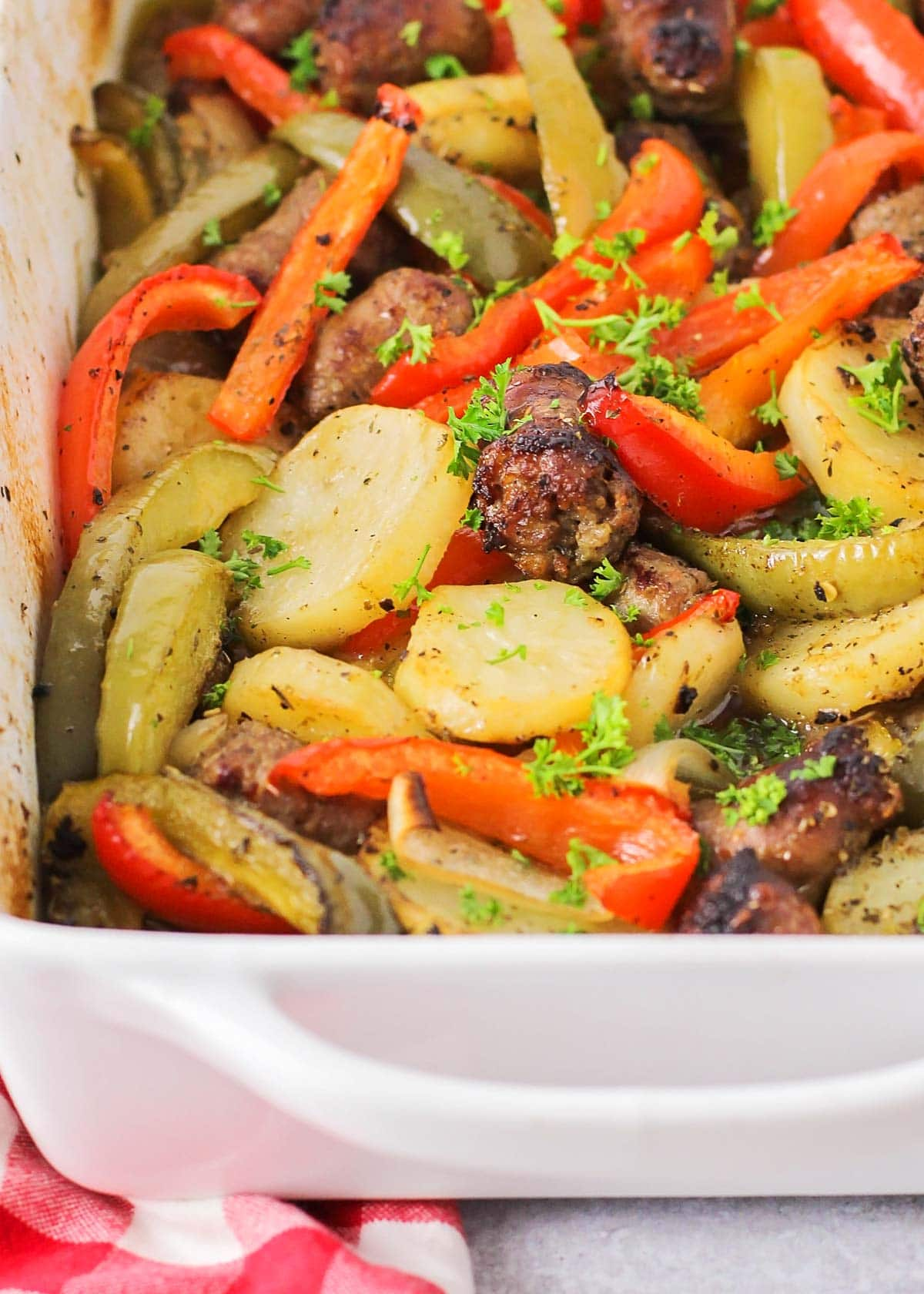 Sausage and potatoes baked in a white casserole dish.